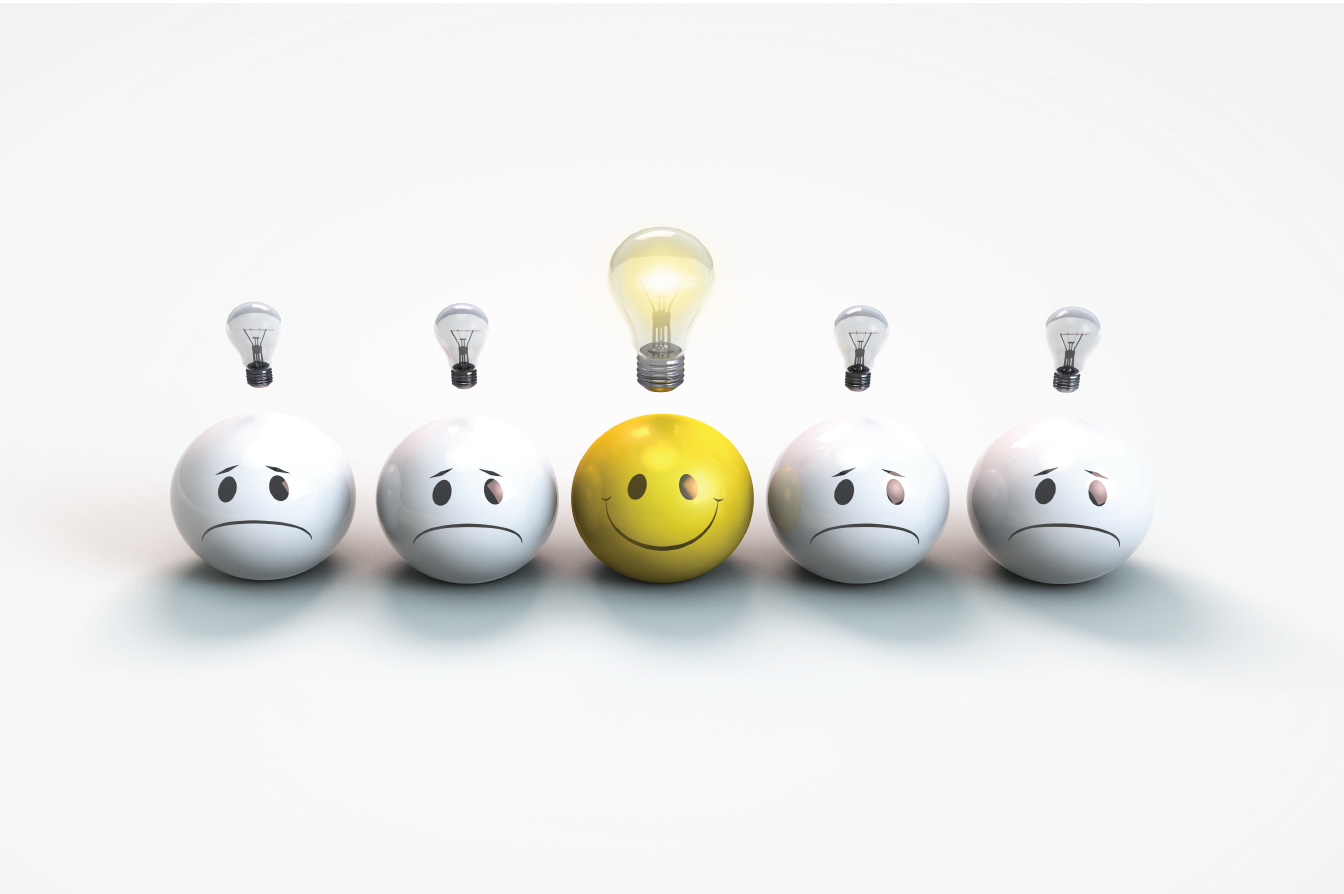 This is a picture of one face smiling with a light bulb illuminated above. The other faces are not smiling and have un-illuminated light bulbs above. Corey Ciocchetti is an inspirational professional speaker who makes audiences think deeply about their happiness, stress reduction, and passions.